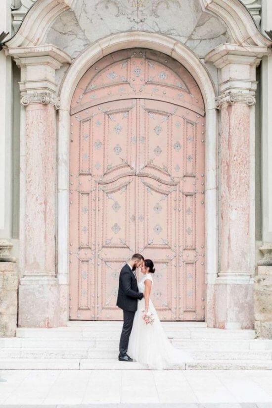 Glückliches Hochzeitspaar vor den romantischen Pforten einer schlossähnlichen Kirche am Hochzeitstag in Augsburg.