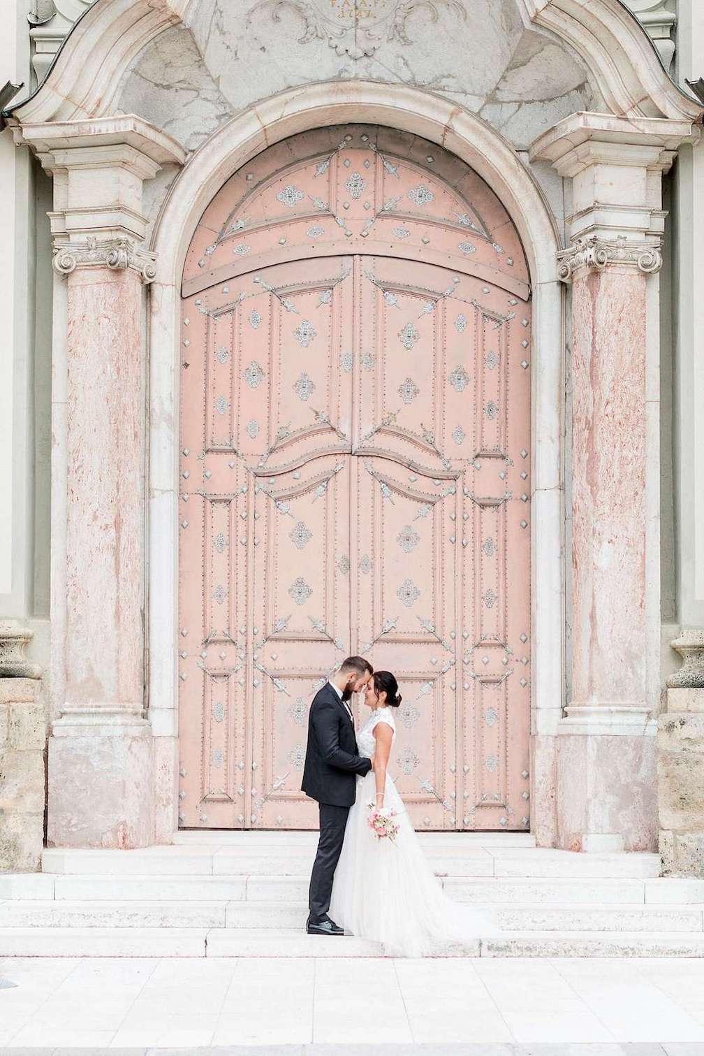 Glückliches Hochzeitspaar vor den romantischen Pforten einer schlossähnlichen Kirche am Hochzeitstag in Ingolstadt.