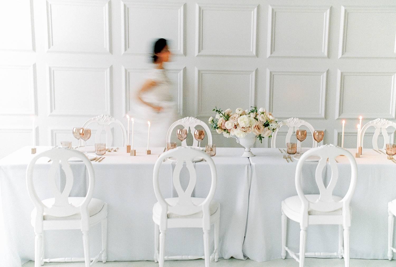 Junge Braut in einem romantischen weißen Brautkleid hinter einer gedeckten Hochzeitstafel in Starnberg.